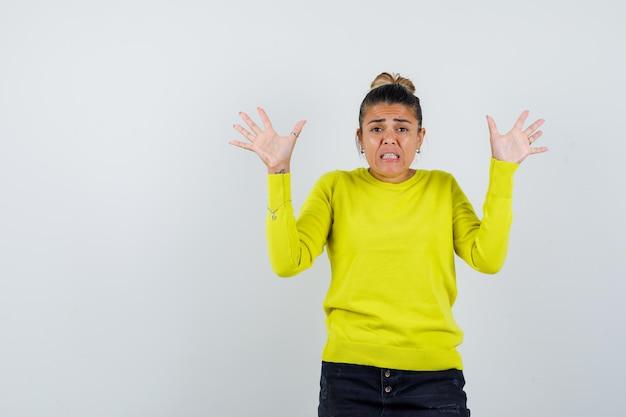 Молодая женщина поднимает руки в желтом свитере и черных брюках и выглядит взволнованной