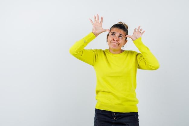 Giovane donna che alza le mani vicino alla testa con un maglione giallo e pantaloni neri e sembra felice
