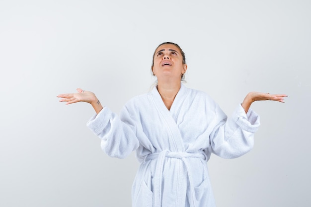 Young woman raising hands to pray in bathrobe and looking hopeful