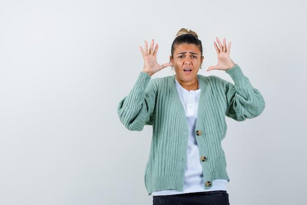 Giovane donna che alza le mani in posizione di resa in camicia bianca e cardigan verde menta e sembra tormentata