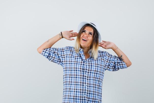 市松模様のシャツで防御するために手を上げて、問題を抱えているように見える若い女性。