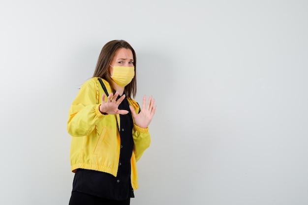 Молодая женщина поднимает руки, чтобы остановиться и выглядит испуганной