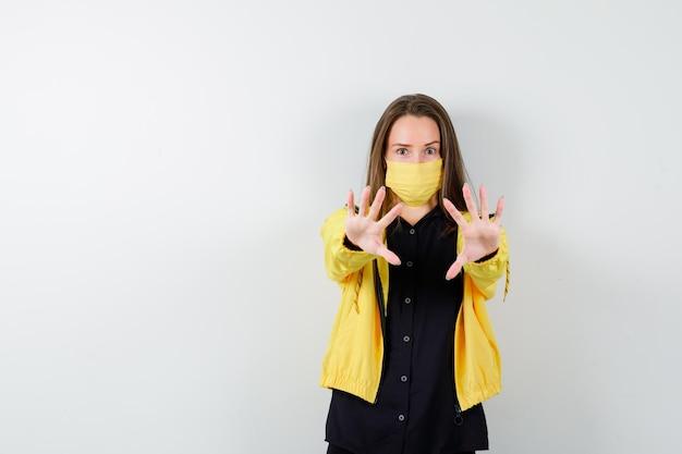 Молодая женщина поднимает руки, чтобы остановить