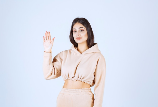 Young woman raising her hand to get noticed