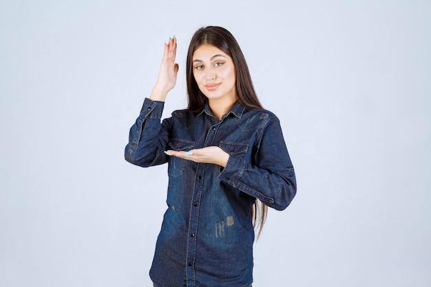 Giovane donna alzando la mano per attirare l'attenzione