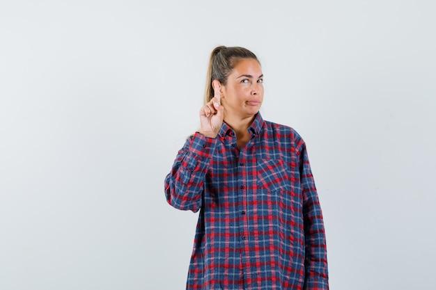 Giovane donna che alza il dito indice in gesto di eureka in camicia a quadri e guardando pensieroso