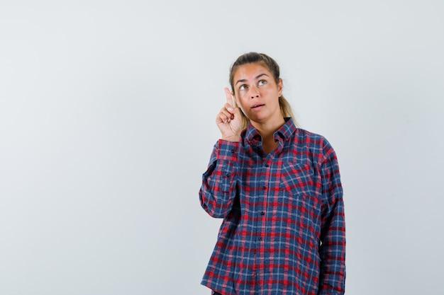 Giovane donna che alza il dito indice nel gesto di eureka in camicia a quadri e sembra carina