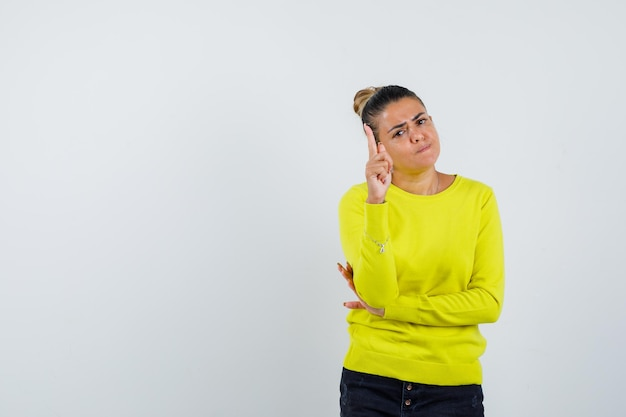 Young woman raising index finger in eureka gesture while holding hand on elbow in yellow sweater and black pants and looking sensible
