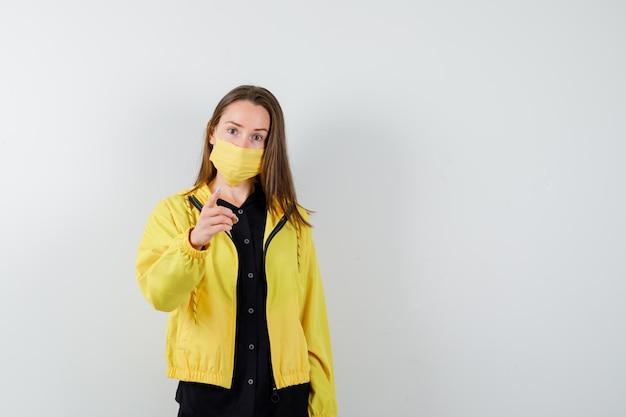 Молодая женщина поднимает указательный палец, чтобы показать жест предупреждения