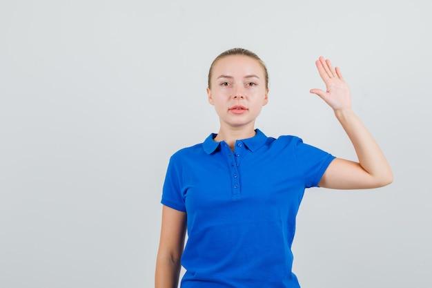 Giovane donna che alza la palma in maglietta blu e che sembra sicura