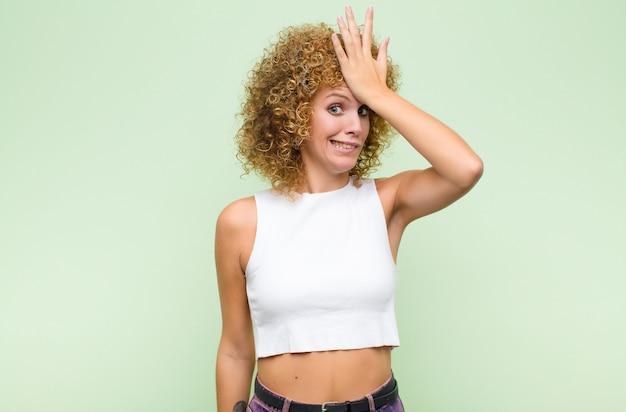 緑の壁に馬鹿げた感覚をしたり、愚かな間違いをしたりした後、額を考えるために手のひらを上げる若い女性