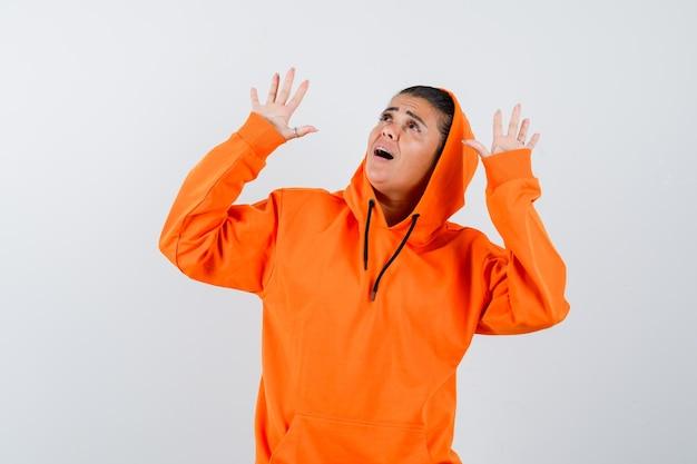 Молодая женщина поднимает ладони в жесте капитуляции в оранжевой толстовке с капюшоном и выглядит удивленно