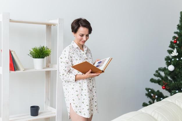 若い女性はクリスマスツリーとリビングルームで本を読む