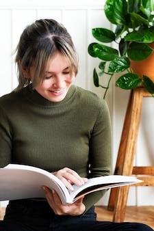 鉢植えの植物に囲まれたガーデニングについての本を読んでいる若い女性
