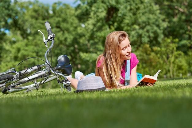 지역 공원에서 자전거를 탄 후 책을 읽는 젊은 여성