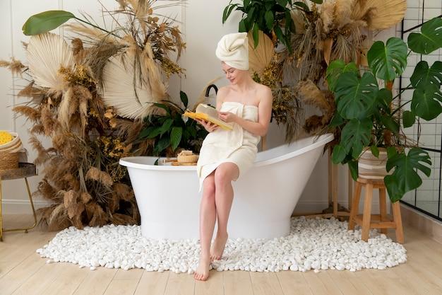 Молодая женщина, читающая книгу после принятия ванны