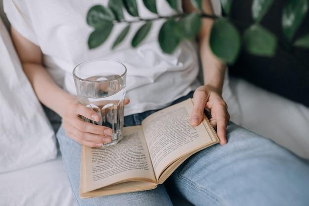 Молодая женщина читает книгу и держит стакан воды крупным планом