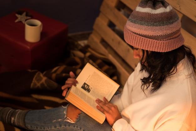 Молодая женщина читает книгу в удобной и непринужденной обстановке с поддоном позади