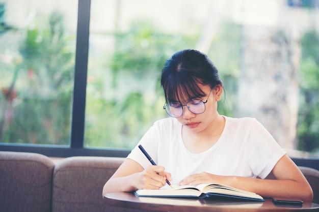 真剣に喫茶店で本を読んでいる若い女性。概念。概念。教育