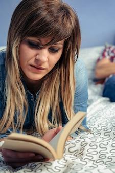 Молодая женщина читает книгу, лежа на кровати, пока ее муж отдыхает