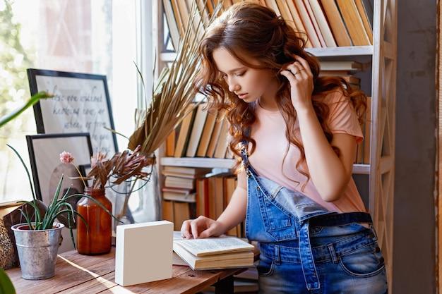 테이블에 흰색 빈 태블릿 책을 읽는 젊은 여자