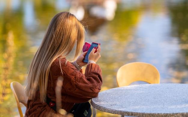 彼女は湖を見下ろすテーブルでリラックスしながら秋の日差しの中で屋外で携帯電話のメッセージを読んで若い女性