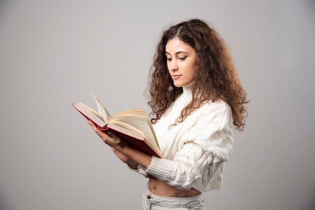 Молодая женщина читает красную книгу на серой стене. фото высокого качества