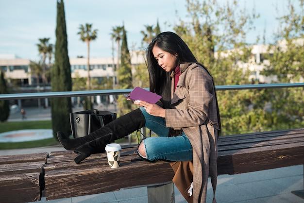 벤치에 앉아 전자책을 읽는 젊은 여성