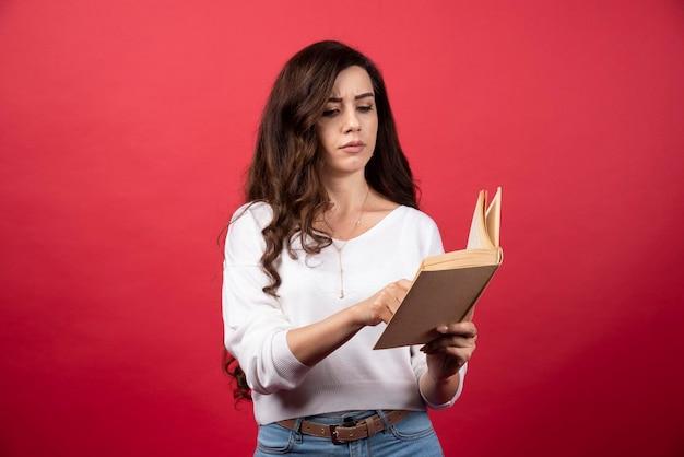 빨간색 배경에 흥미로운 책을 읽는 젊은 여자. 고품질 사진