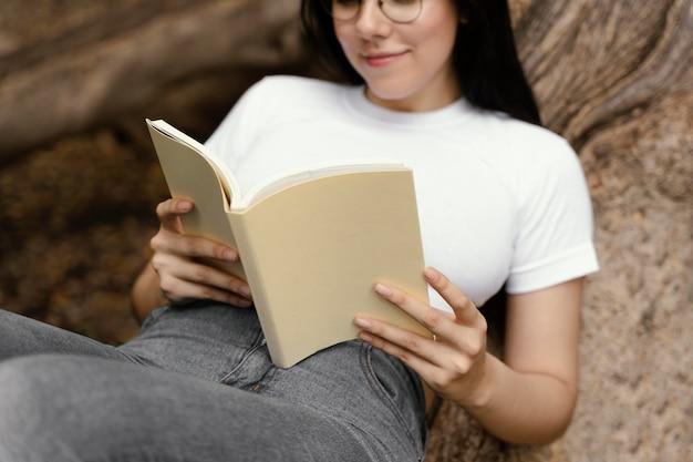 야외에서 흥미로운 책을 읽는 젊은 여자