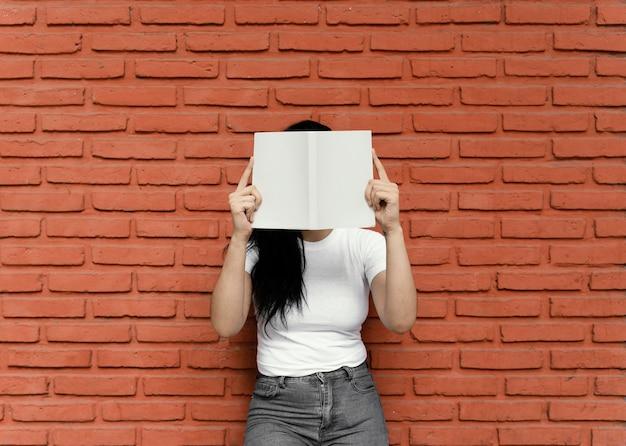 屋外で面白い本を読んでいる若い女性