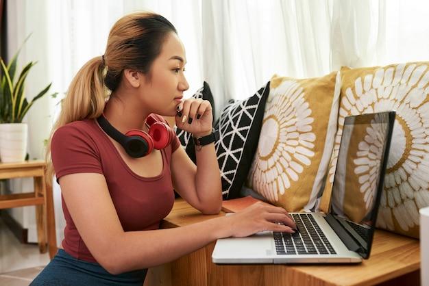 노트북에 기사를 읽는 젊은 여자