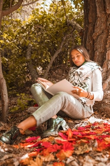 Young woman reading in autumn forest