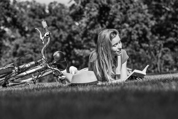 Young woman reading a book after cycling at the local park
