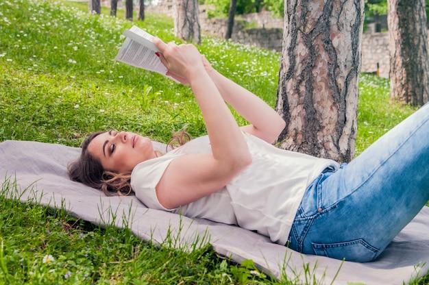 Молодая женщина, чтение книги в парке, лежа на траве. селективный фокус. молодая красивая внимательная женщина лежит на зеленой траве и читает книгу против городского парка.