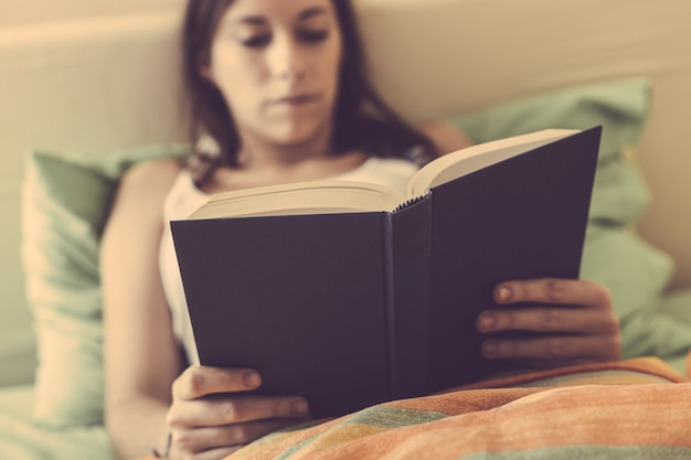 Young woman reading a book on the bed