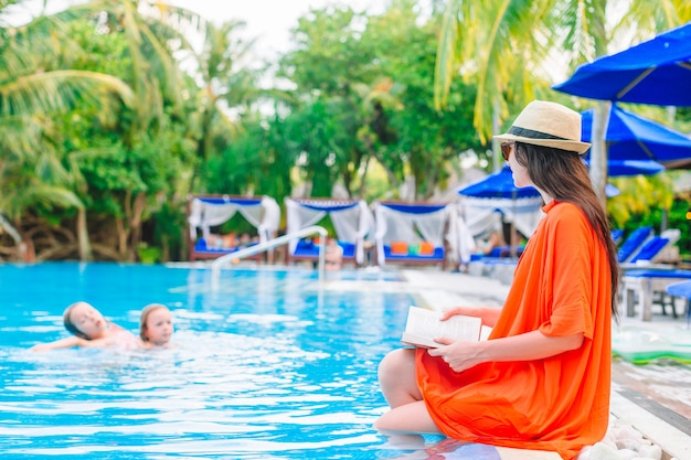 Young woman reading book by the swimming pool