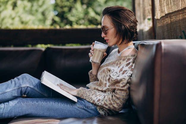 Young woman reading book and drinking coffee