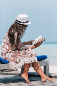 Young woman reading book during tropical maldivian beach