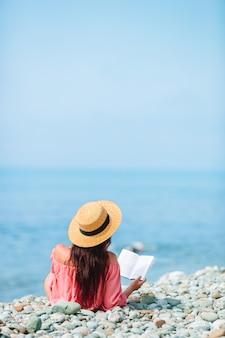 Книга чтения молодой женщины во время тропического белого пляжа
