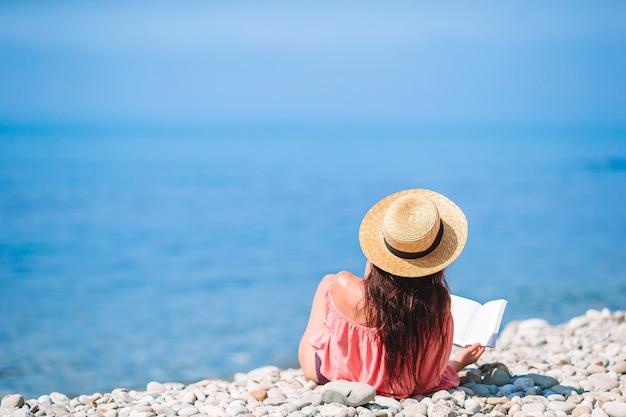 熱帯白いビーチの中に本を読む若い女性