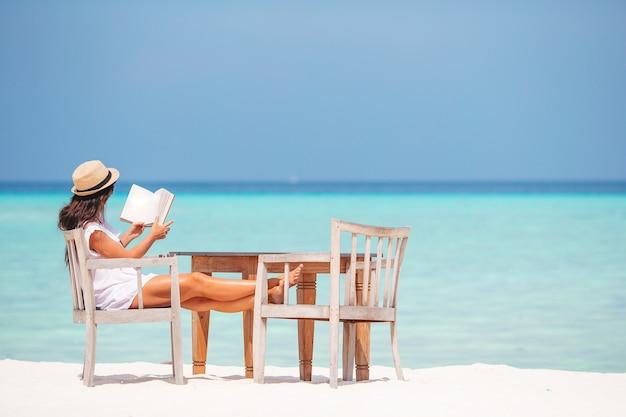 열대 하얀 해변에서 책을 읽는 젊은 여성