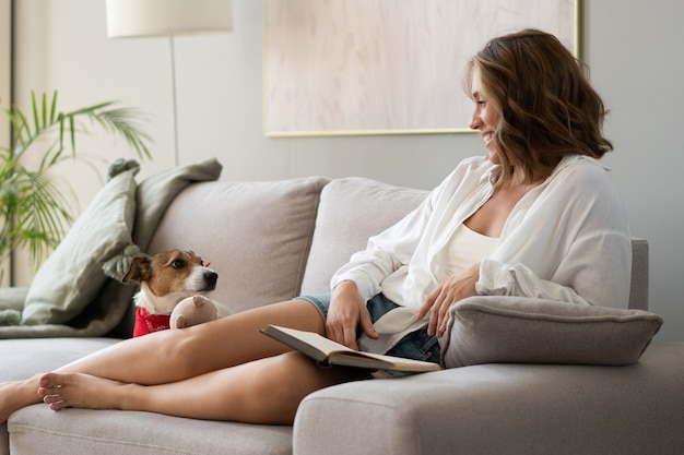 Young woman reading book and her cute dog on sofa at home. lovely pet.