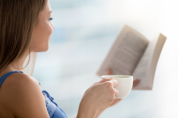 Young woman reading book, holding cup of coffee