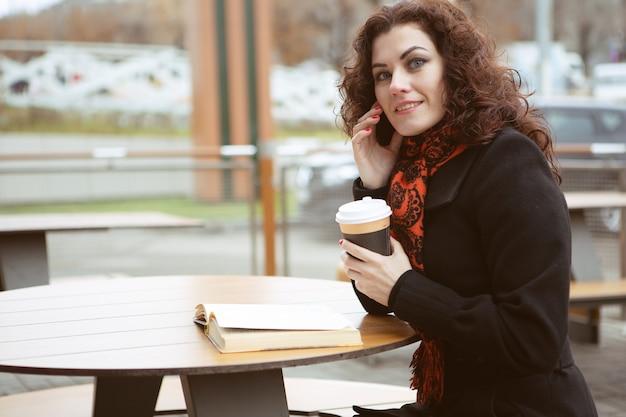 ストリートカフェで本を読んで若い女性