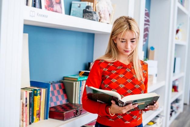 Молодая женщина, чтение книги в библиотеке