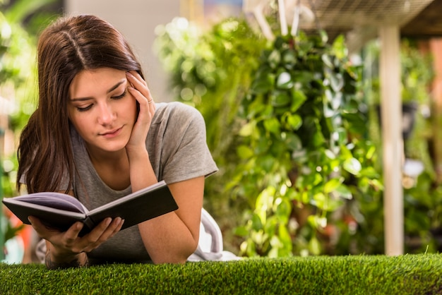 Young woman reading book and lying on lawn