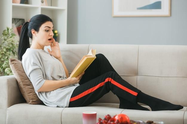 リビングルームのコーヒーテーブルの後ろのソファに横たわって本を読んで若い女性