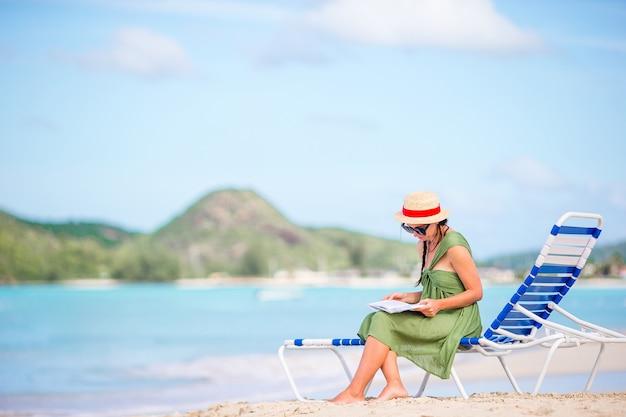 Книга чтения молодой женщины на шезлонге на пляже