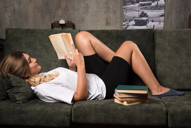 幸せな表情でソファで本を読んでいる若い女性。